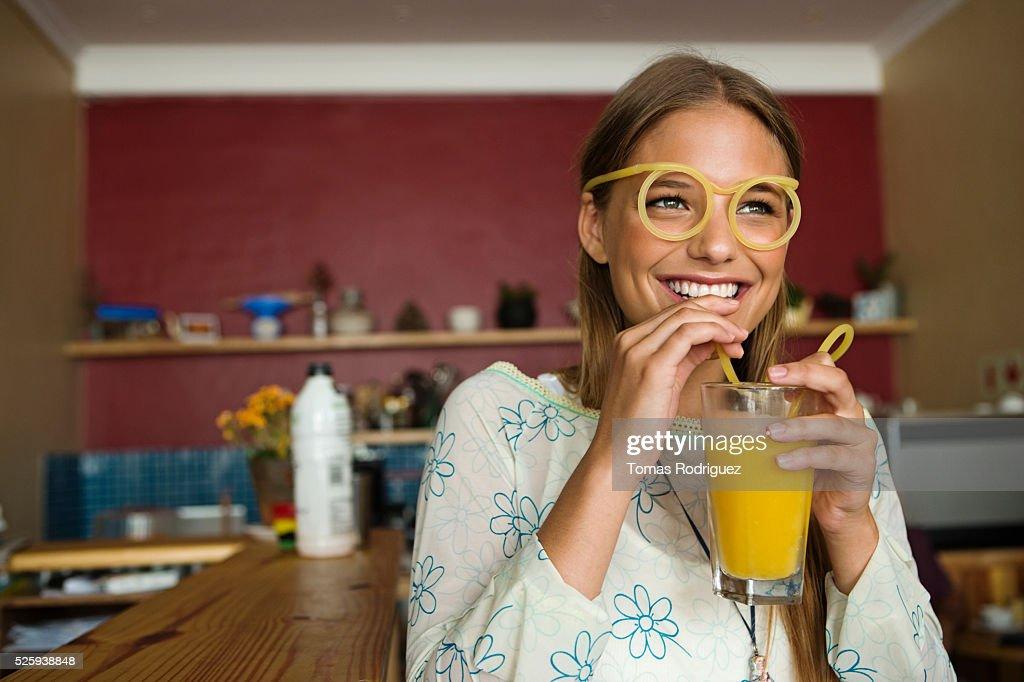 Woman drinking orange juice : Bildbanksbilder
