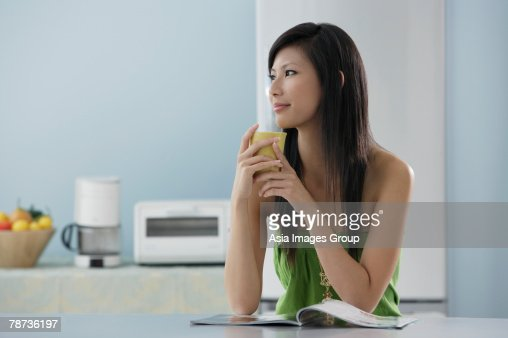 Woman Drinking Out Of Mug In Kitchen With Magazine Stock