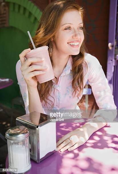 Woman drinking smoothie in outdoor cafe