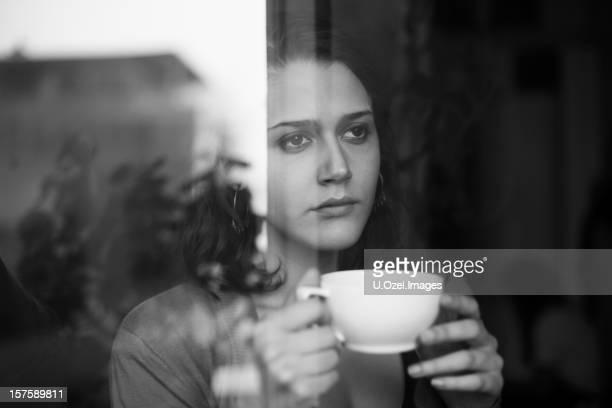 Woman drinking tea looking outside the window