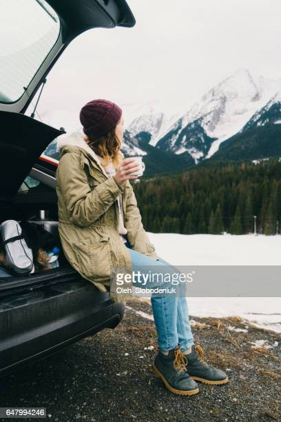 Woman drinking tea or coffee near the car in winter