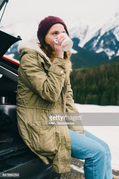 Woman drinking tea or coffee near the car in winter