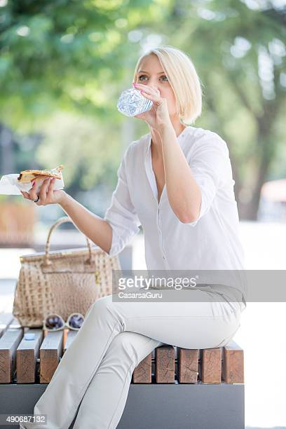 Woman Drinking Water and Eating Slice of Pizza Outdoors