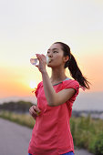 Woman drinking water at sunset.