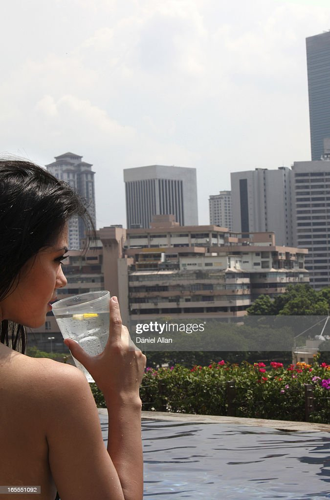 Woman drinking water by pool : Stock Photo