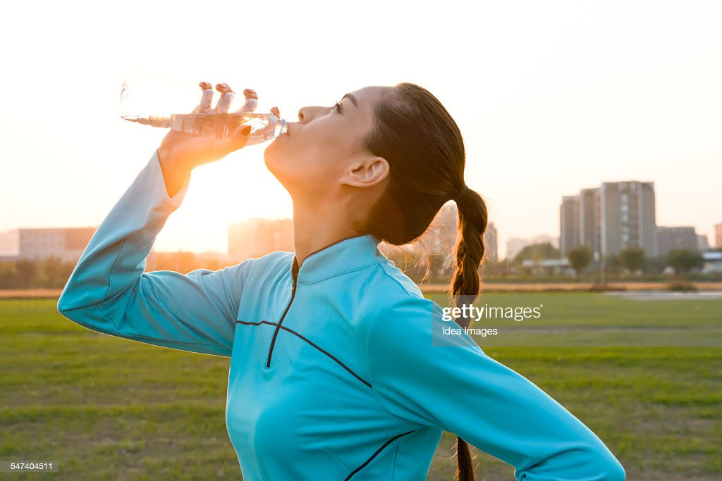 Woman drinking water during jogging : Stock Photo