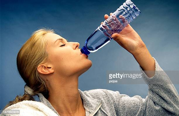 woman drinking water from the bottle