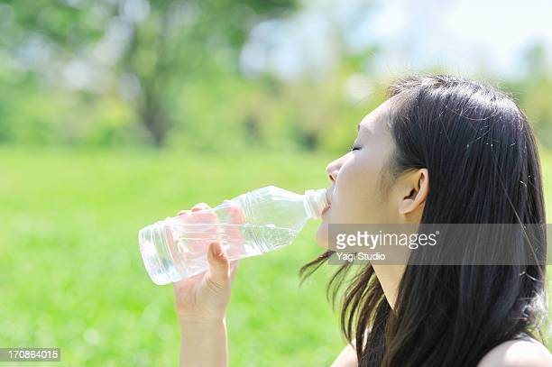 Woman drinking water  in nature