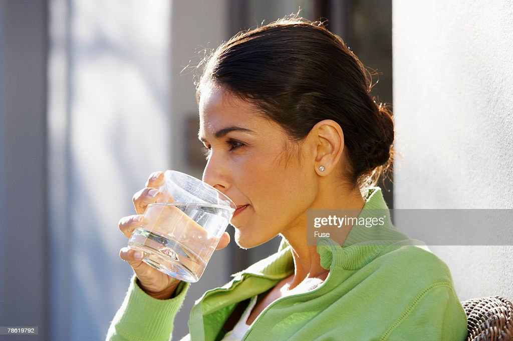 Woman Drinking Water Outside Home
