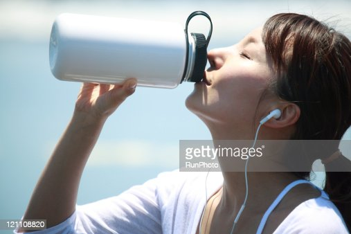 Woman drinking water&listening to music at the sea : Stock Photo