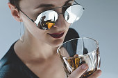 close-up view of beautiful young woman in sunglasses drinking whiskey isolated on grey