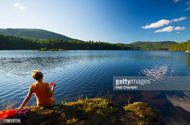 Woman Drinking Wine on Shore of Mountain Lake