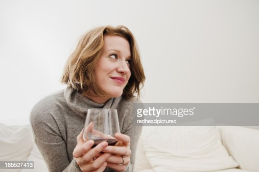 Woman drinking wine on sofa : Stock Photo