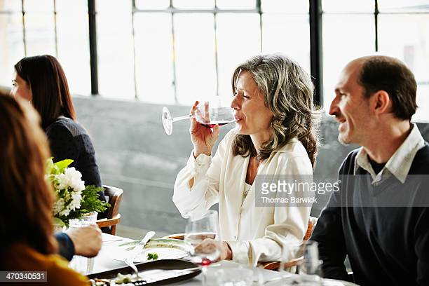 Woman drinking wine with friends at dinner party