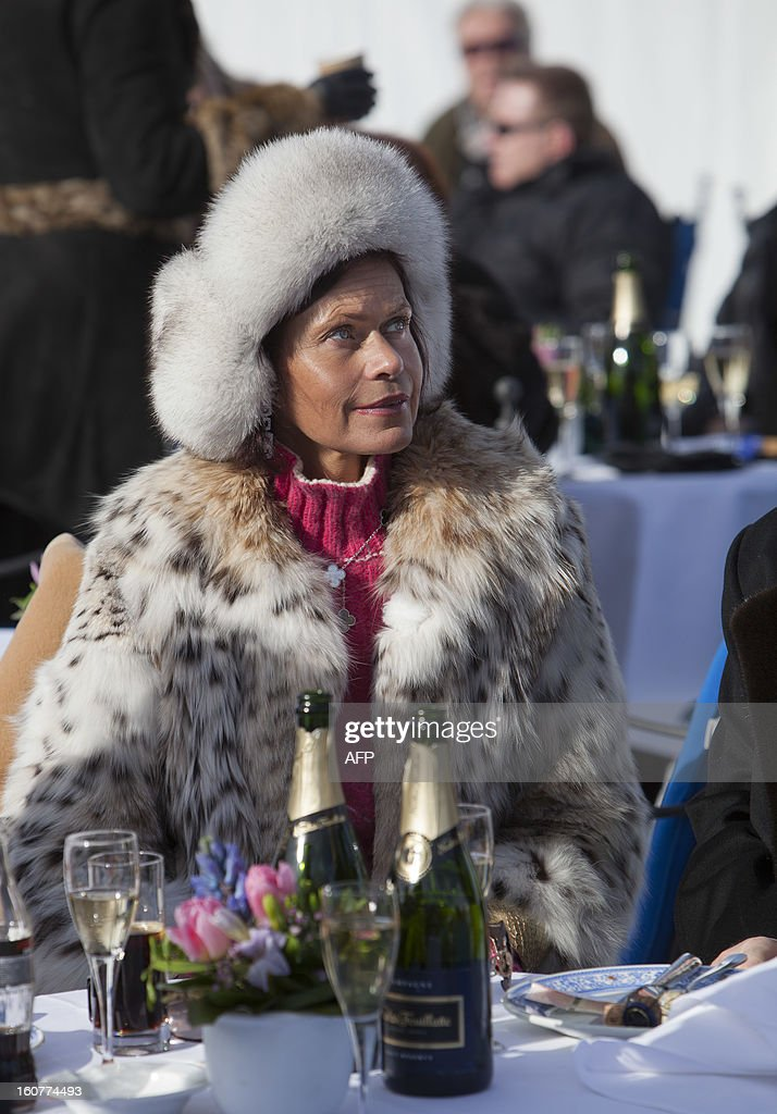 PEDRERO---A woman drinks champagne at the White Turf horse racing event in St. Moritz on February 3, 2013. The races are held on the frozen lake of the Swiss mountain resort and are famous among the jet set.
