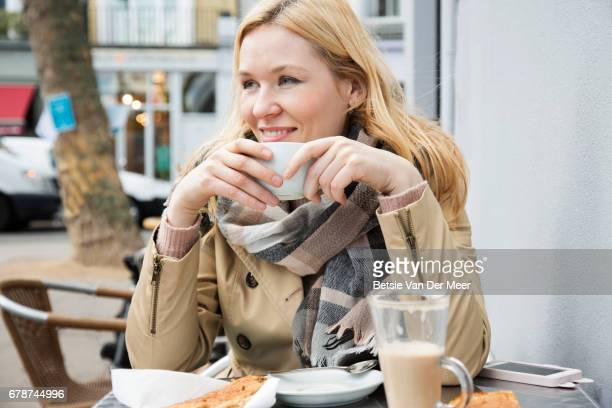 Woman drinks coffee in pavement cafe in city.
