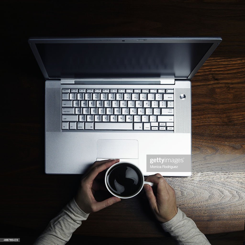 Woman drinks coffee while waits for computer : Stock Photo