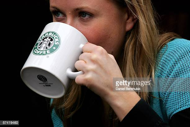A woman drinks from a coffee mug in A Starbucks store in central London on April 25 2006 in London England The all traditional English style...
