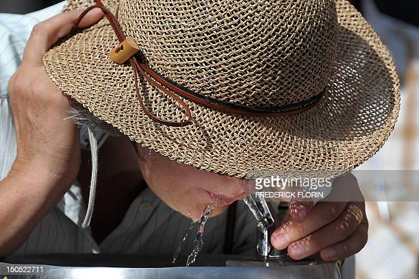 A woman drinks water from a public fountain on August 20 2012 in Strasbourg eastern France French authorities are keeping an eye on isolated elderly...