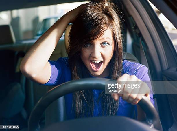 Woman driver gasps in surprise or horror, hand clutching head