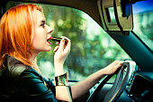 Concept of danger driving. Young woman driver red haired teenage girl painting her lips doing make up while driving the car.