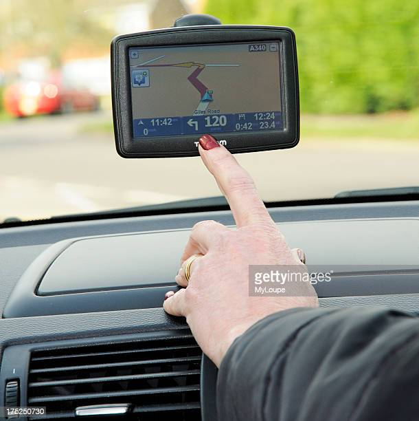 Woman driver using a TomTom satellite navigation device