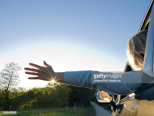 Woman drives along country road at sunrise