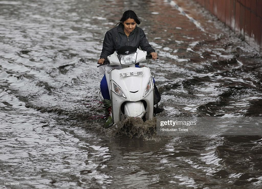A woman drives her vehicle through a water logged road at Akshardham Area on February 5, 2013 in New Delhi, India. The persistent rains since late last night break the seven decade old record for the highest rainfall in a single day in February and triggeredmassive traffic jams due to water-logging across the city.