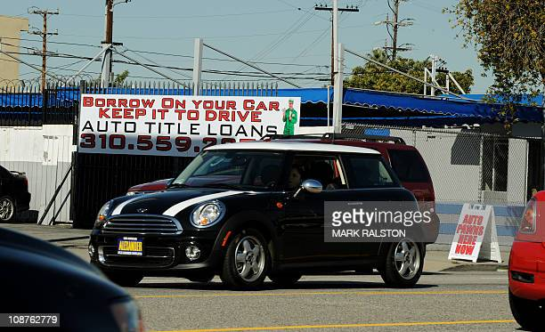 A woman drives past a firm offering cash loans which use your car as collateral in Los Angeles on February 02 2011 The United States is poised to hit...