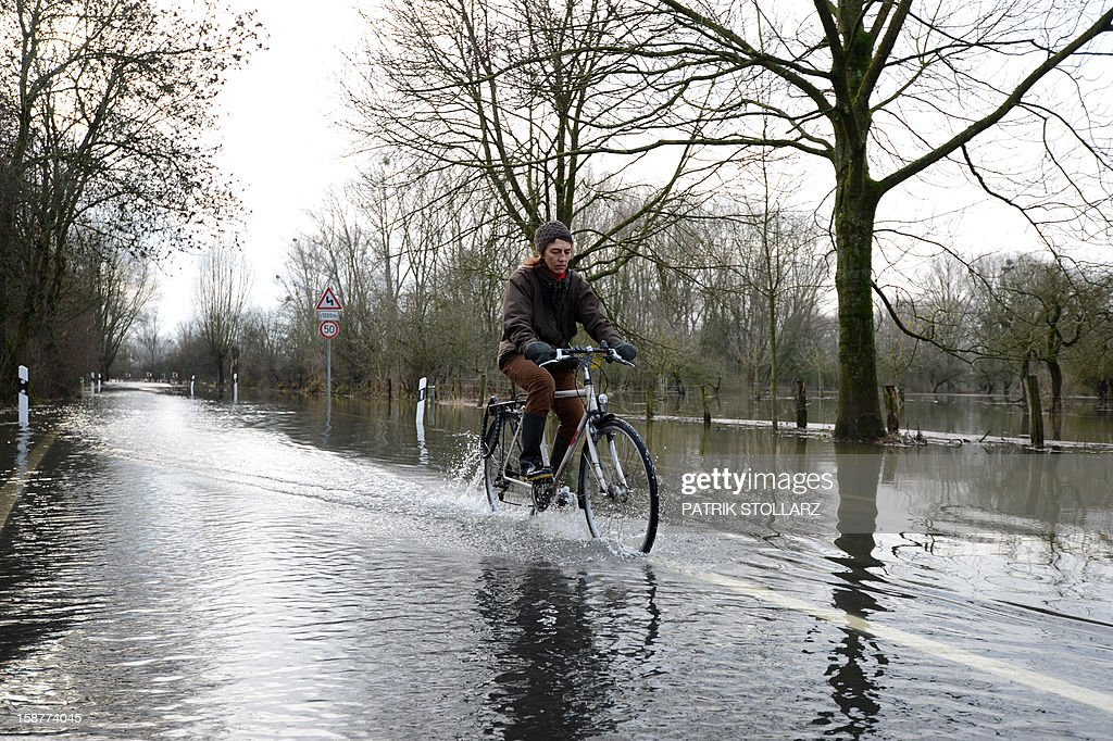 A woman drives with her bike through a flooded street near the river Rhine on December 28, 2012 near Duesseldorf, western Germany.