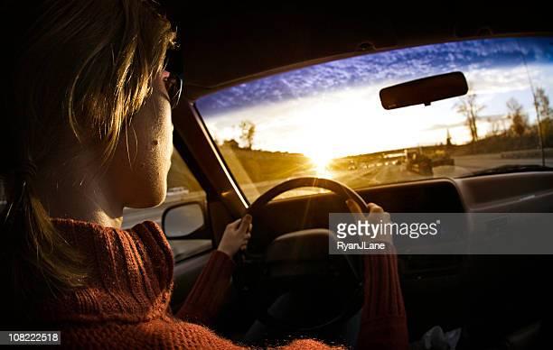 Woman Driving a Car At Sunset