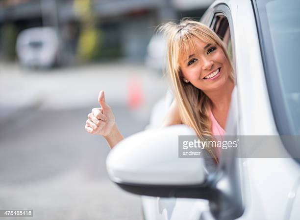 Woman driving a car with thumbs up