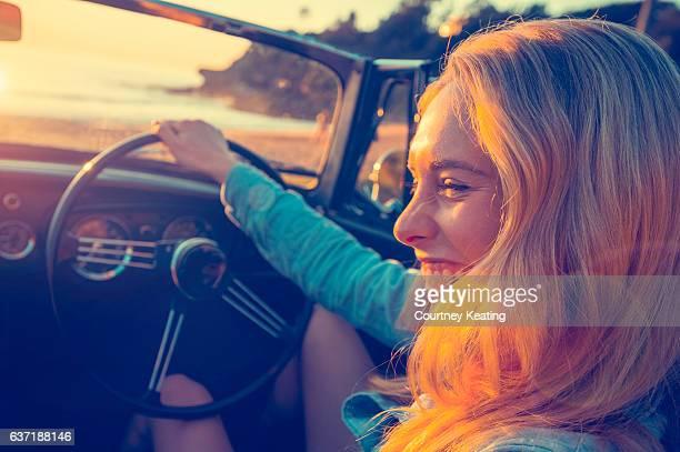 Woman driving a convertible at the beach