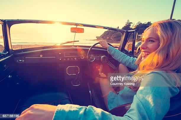 Woman driving a convertible at the beach.