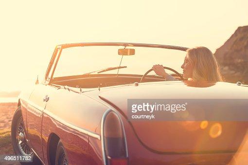 Woman driving a convertible car at the beach.