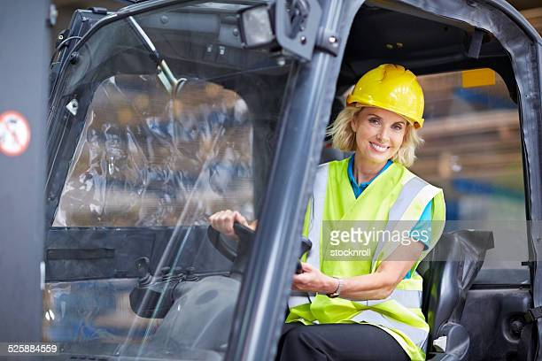Woman driving a forklift at distribution warehouse