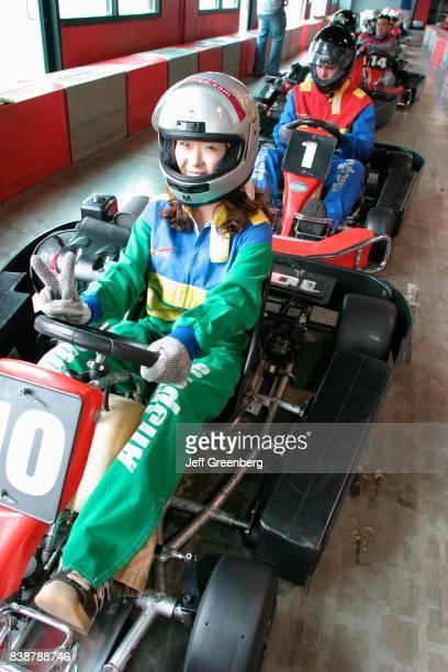 A woman driving a go kart at the Grand Prix Allsports Hi Speed Indoor Kart Racing