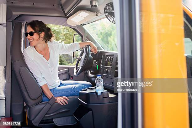 Woman driving a school bus ready to go.