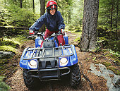 Woman driving ATV through forest