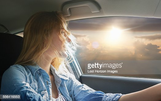 Woman driving car and watching sunset