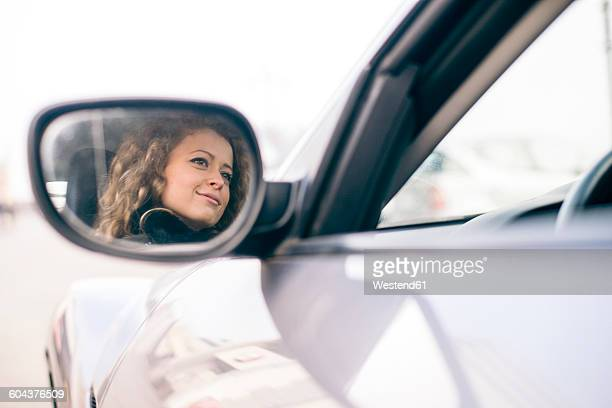 Woman driving car, mirrored in wing mirror