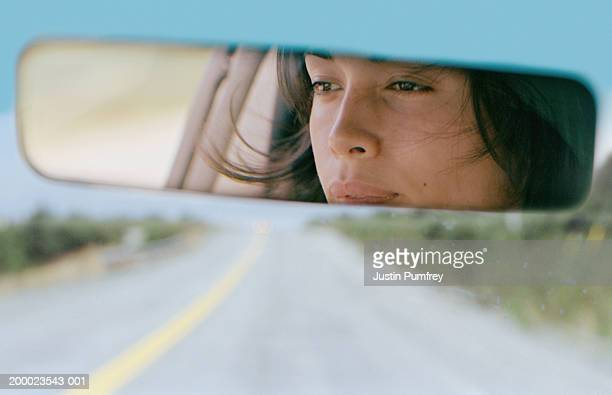 Woman driving car reflected in rear view mirror, close-up