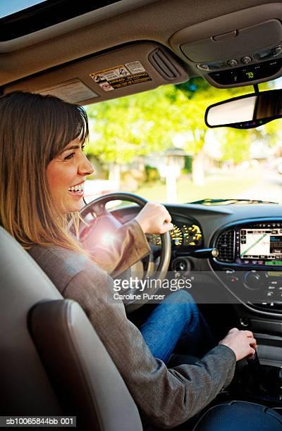 Woman driving car, smiling, profile