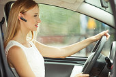 Transport and safety concept. Young blonde woman driving car using her mobile phone and headset, side view