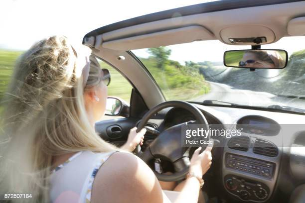 Woman driving car with roof down