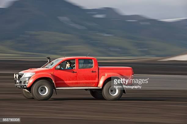 Woman driving customized pick up truck on Maelifellssandur area on the Icelandic highlands