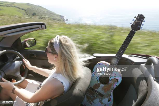 Woman driving in car on coast road with roof down and guitar in back