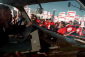 A woman driving is stopped by a mass rally of striking suburban janitors of the Service Employees International Union April 2000 in Oak Brook IL The...