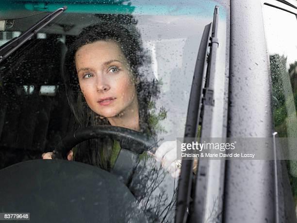 Woman driving, rain falling