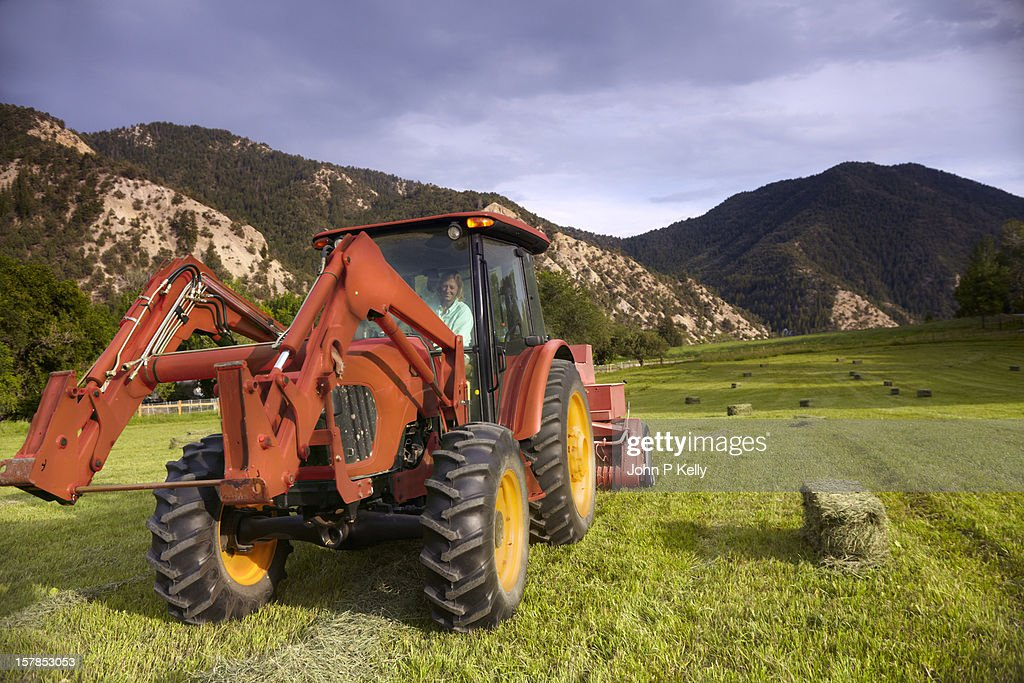 Woman driving tractor, baling hay : Stock Photo